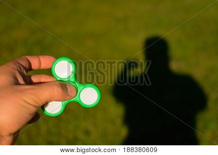 Spinner in male hands on a background of green grass and shadow man on a sunny day.