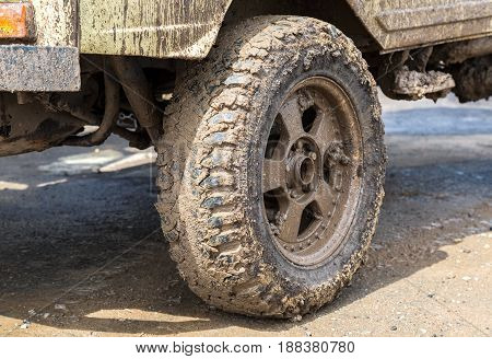 Extremely dirty SUV wheel after driving in the rain on dirty rural road