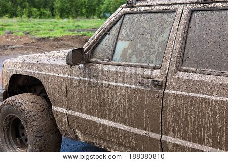 Dirty SUV after driving in the rain on extremely dirty rural road