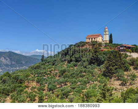 Beautiful view on orange roofing temple church on top of green hills mountains on Greece island Zakynth and blue sky. Greece landscape. Greece tourism holidays vacation tours. Church on hill