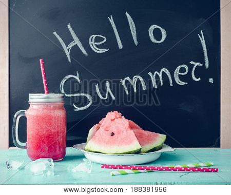 Hello summer written on the blackboard with watermelon juice in glass mason jar with slices of watermelon and ice on blue background. Fresh fruit flavored cold smoothie. Start Summer Concept.