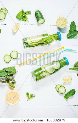 Cold and refreshing infused detox water with lime mint and cucumber in a bottle on white wood background.