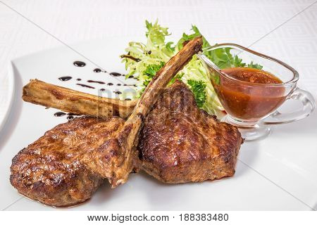 Delicious barbecue. Appetizing pieces of roasted meat on bones herbs and sauce on a white plate