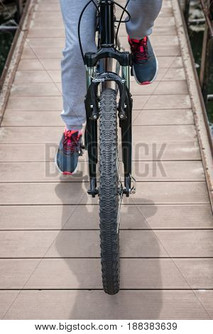 A Trip By Mountain Bike Along The Bridge Across The River. Sports And The Concept Of Active Life In