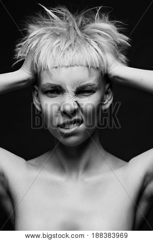 Close up on face of crazy mad cocky young woman with stylish dyed pink hair, hands ruffle her haircut angry and bold expression.