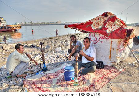 Bandar Abbas Hormozgan Province Iran - 16 april 2017: Three men rest on the beach two of them smoke a hookah.