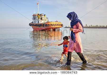 Bandar Abbas Hormozgan Province Iran - 16 april 2017: A young woman walks along the shore of the Persian Gulf with her child against the background of an orange towboat standing on the shallows.