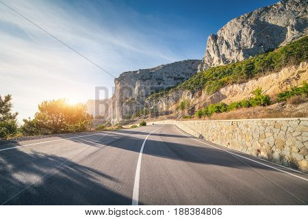 Asphalt road in summer at sunrise. Landscape with beautiful empty mountain road with a perfect asphalt high rocks trees and sunny blue sky. Travel background. Highway at mountains. Transportation