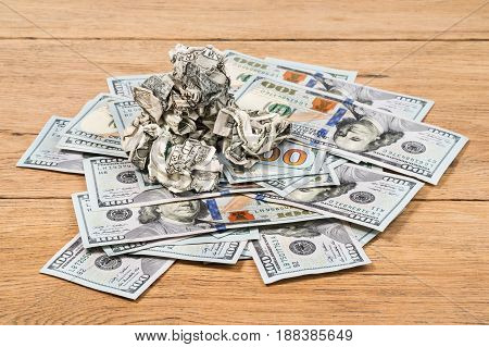 Crumpled money on a pile of new dollars lying on an old table