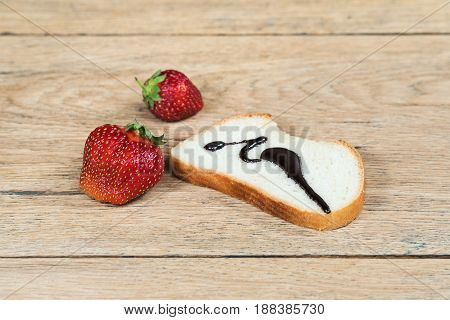 Ripe strawberries lies on an old wooden table next to a piece of white bread poured hot chocolate