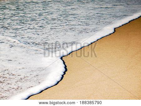 Foamy wave slowly rolls in on sandy beach in Ventura CA