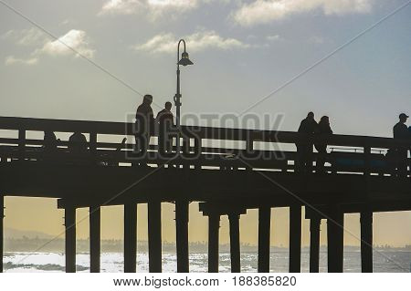 Silouette of people on wooden pier in early morning