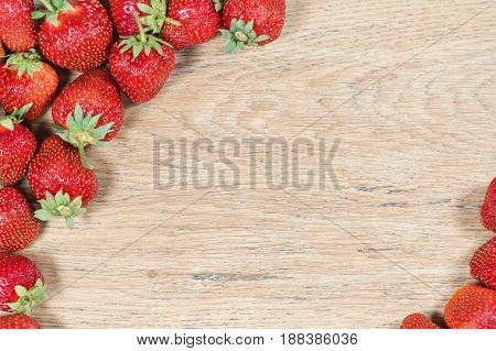 Old wooden texture with ripe strawberries in the corners as a decorative background