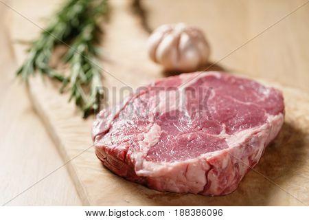 raw rib eye steak on board closeup, shallow focus