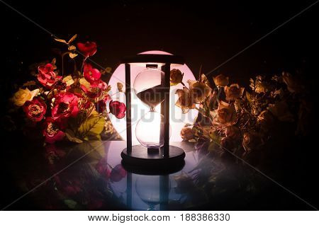 Time concept. Sand passing through the glass bulbs of an hourglass measuring the passing time as it counts down to a deadline. Silhouette of Hourglasses in smoke on dark background