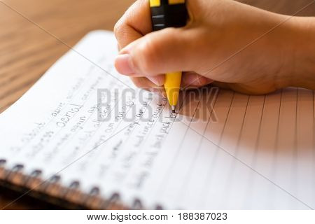 Child Writing By Hand On Notepad