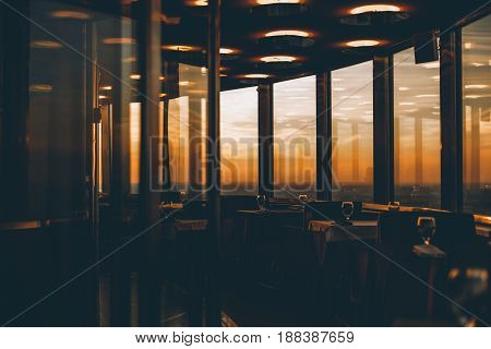 Dark empty chrome and glass interior of luxury restaurant located on the top of skyscraper with stunning orange sunset and beautiful view of cityscape outside the panoramic windows