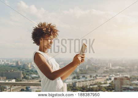 Laughing beautiful afro american teenage girl is making panorama image on her digital tablet while standing on observation point of high building with cityscape in blackground on warm sunny day