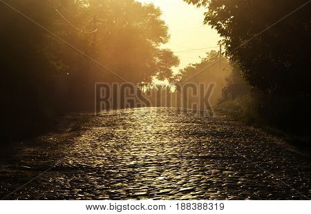 Dust on the stone road. Rural road paved with paving stones.