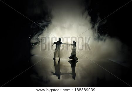 Silhouettes Of Toy Couple Dancing Under The Moon At Night. Figures Of Man And Woman In Love Dancing