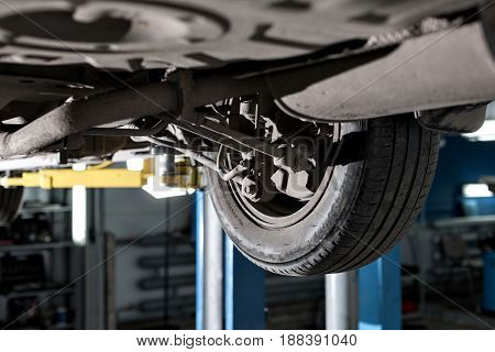 rear car suspension. the garage mechanic raised the car on the lift.