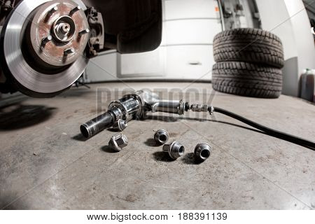 air gun to tighten a tire bolts on a suspended car at an auto shop.