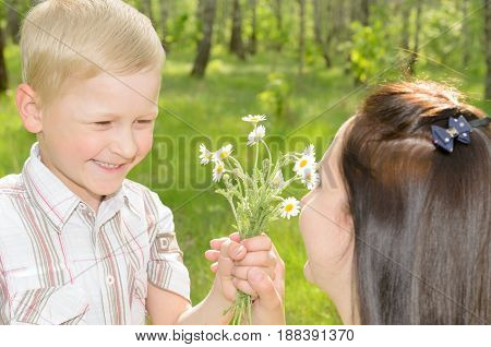 The boy gives flowers to his mother