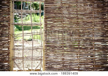 A self-made garden fence made of intertwined branches. A self-made garden fence made of intertwined branches.