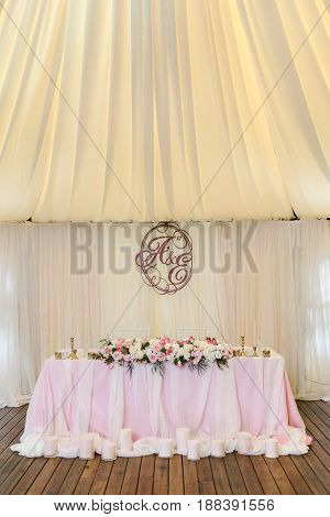 Gorgeously decorated newlyweds table with flowers, candles and monogram under it