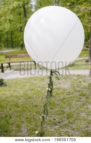 Air balloon in park, with decorated with petals thread, closeup