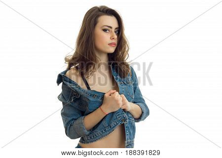 charming brunette stands before the camera with a denim jacket undone close-up isolated on white background