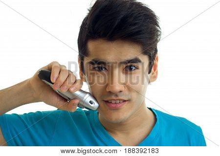 Portrait of a handsome young guy who looks at the camera smiling and shaves the beard trimmer close-up isolated on white background