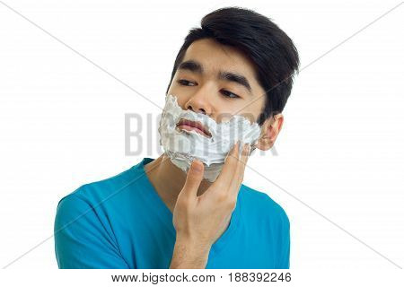 beautiful narcissistic guy looks away and putting a beard foaming close-up isolated on white background