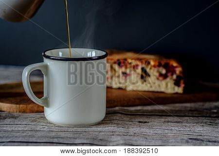 Fresh coffee in a white mug with a fruit pie