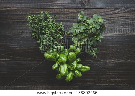 Fresh herbs in heart shape on the dark wooden table, top view.