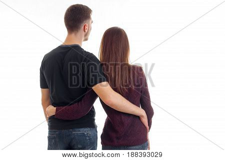 a young couple standing with his back to the camera and cuddling close-up isolated on white background
