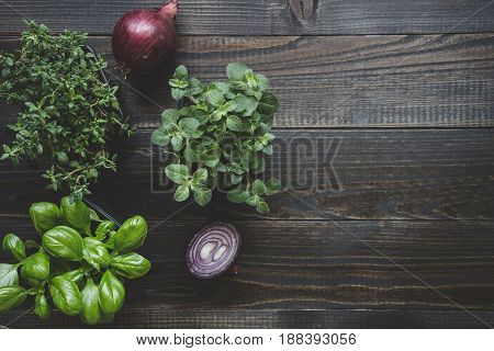 Fresh herbs with red onion on the wooden background with copy space.