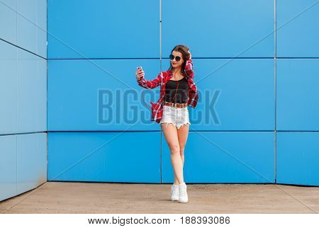 Fashion portrait of pretty smiling hipster girl in sunglasses with smartphone and headphones making selfie against the colorful blue wall
