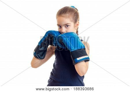 little girl in boxing gloves practicing and looking at the camera isolated on white background