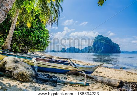 Boat on shore under palms for repair. Tropical island landscape, El- Nido, Palawan, Philippines, Southeast Asia