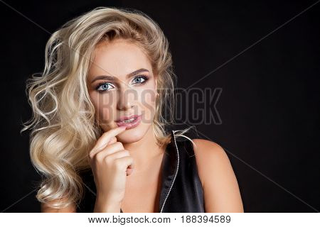 Beauty portrait of elegant young woman. Dark background. Girl looking at camera. Glamour makeup. Studio