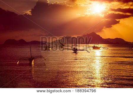 Traditional filippino boats at El Nido bay in sunset lights. Palawan island, Philippines.