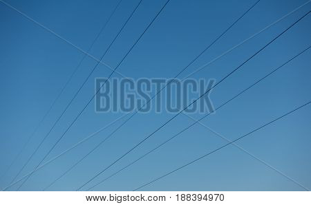 High voltage power wires against sky network. Blue clear sky and electric cables.
