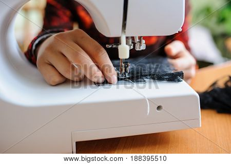Young woman sewing with sewing machine while sitting at her working place in fashion workshop