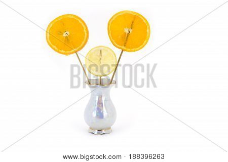 Lemon and orange slices, fixed in a vase as flowers, in a graceful small vase isolated on white background