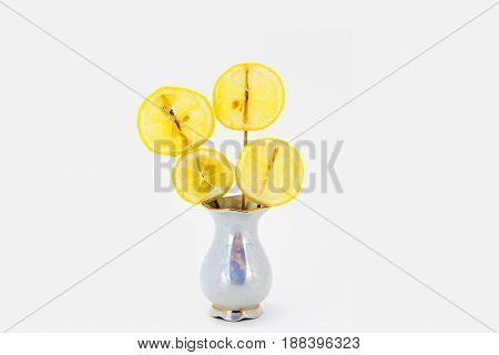 Lemon slices, fixed in a vase as flowers, in a graceful small vase isolated on white background