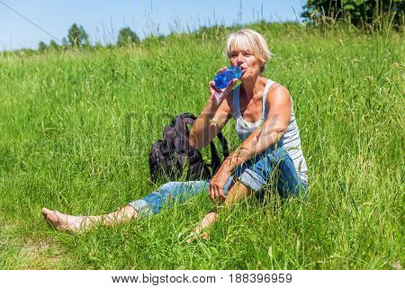 Mature Woman Drinks Water At A Hiking Rest