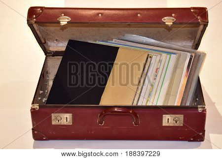 open vintage red suitcase with brass buckles and music records vinyl inside