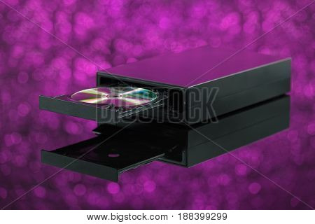 Black CD DVD burner on purple background. Front view