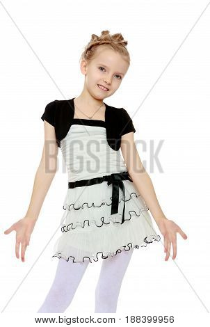 Beautiful little blonde girl dressed in a white short dress with black sleeves and a black belt.The girl parted in the side of the palm.Close-up.Isolated on white background.